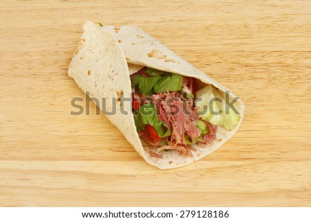 Pulled pork and salad bread wrap on a wooden board - stock photo