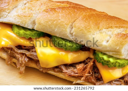Pulled pork baguette sandwich with cheese, cucumber and bbq sauce closeup - stock photo