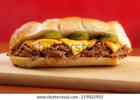 Pulled pork baguette sandwich with cheese, cucumber and bbq sauce , red background  - stock photo
