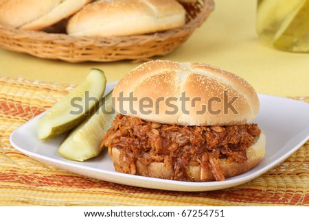Pulled pork barbecue sandwich with pickles on a plate