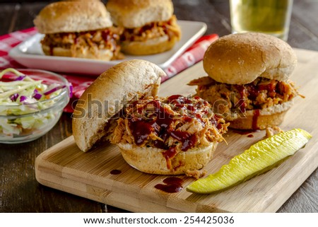 Pulled pork barbeque sliders sitting on wooden cutting board with dill pickle and additional sliders in background with beer - stock photo