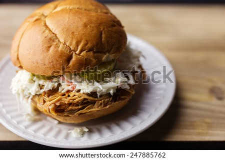 Pulled pork BBQ sandwich with sweet pickles and coleslaw on a white plate.  - stock photo