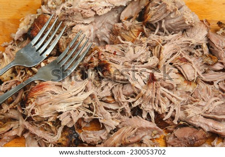 Pulled pork being shredded on wooden carving board. - stock photo