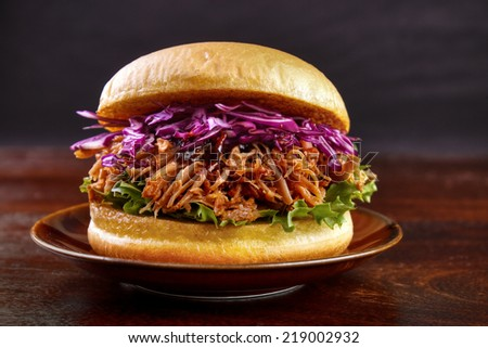 Pulled pork burger with red cabbage salad and bbq sauce on plate with dark background  - stock photo