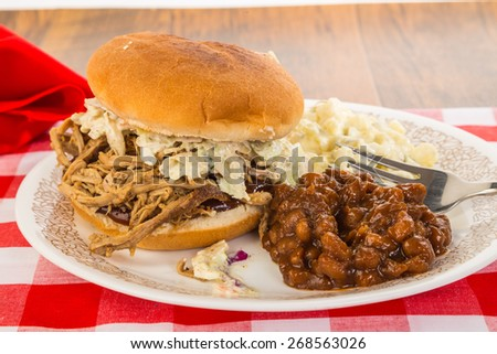 Pulled Pork on Bun with barbecue sauce and coleslaw.  Served with southern style baked beans and potato salad on picnic table with red plaid tablecloth. - stock photo