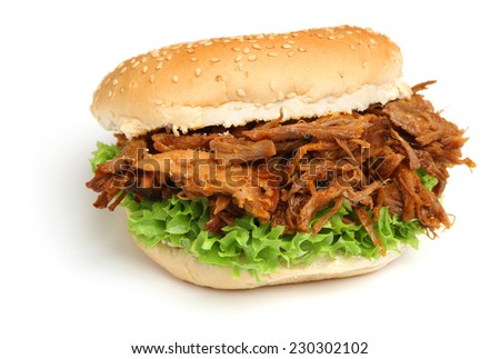 Pulled pork sandwich in a sesame seed roll.