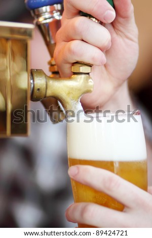 Pulling a beer tap on a fountain at a bar.