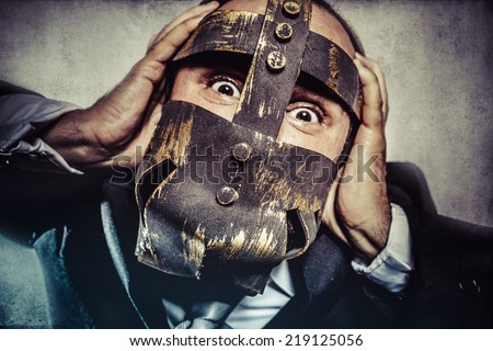 pulling, dangerous business man with iron mask and expressions - stock photo