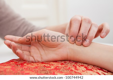Pulse diagnostic with hand on a cushion - stock photo