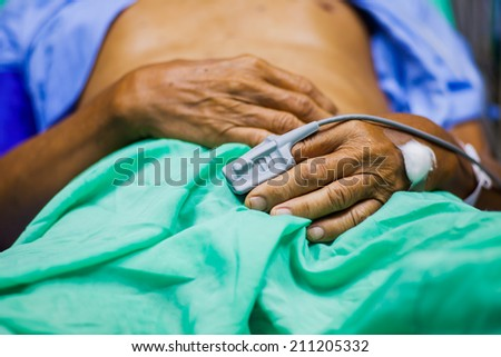 Pulse oximeter sensor on the patient's hand - stock photo