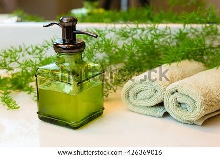 Pump green glass bottle with liquid castile soap. Rolled green towels in a spa setting. Green plant decor in background. Bathroom white countertop. - stock photo