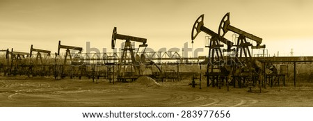 Pump jack group and wellheads. Extraction of oil. Toned. - stock photo