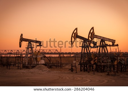 Pump jack group on a sunset sky background. Extraction of oil. Toned. - stock photo