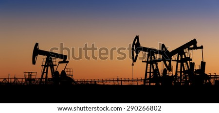 Pump jack group silhouette on a sunset sky background. Extraction of oil. Toned. - stock photo