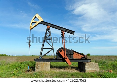 Pump Jack in a green field - stock photo