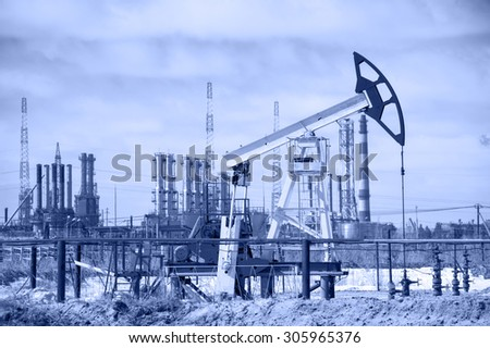Pump jack on a background of petrochemical plant. Oil and gas industry. - stock photo
