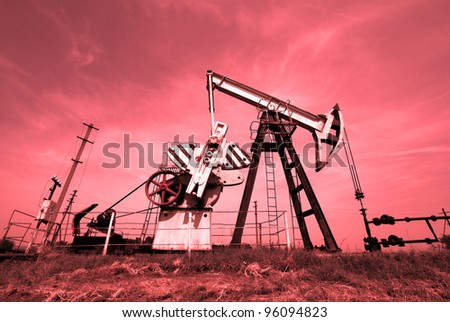 Pump jack on a oil field. Colorize in red - stock photo