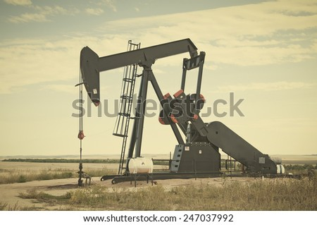 Pump jack starting the lifting stroke to brink crude oil up out of a producing oil well. Retro instagram look.