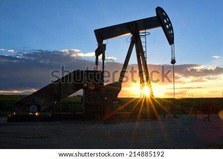 Pump Jack with the sun and setting in the background on a summer evening. The sun rays bursting through the oil rig - stock photo
