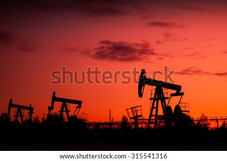 Pump Jacks at sunset sky background. Selective focus, shallow depth of field. - stock photo