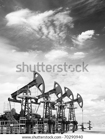 Pump jacks on a oil field. Black and white photo - stock photo