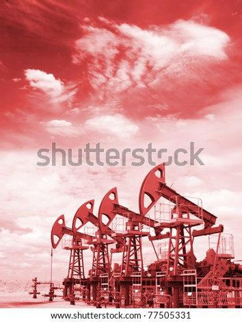 Pump jacks on a oil field. Colorize in red - stock photo