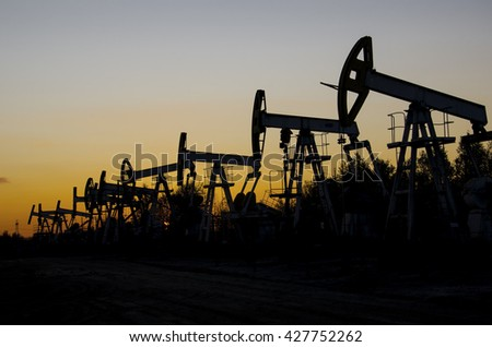 Pump jacks silhouettes during sunset on the oilfield. Oil and gas concept. - stock photo