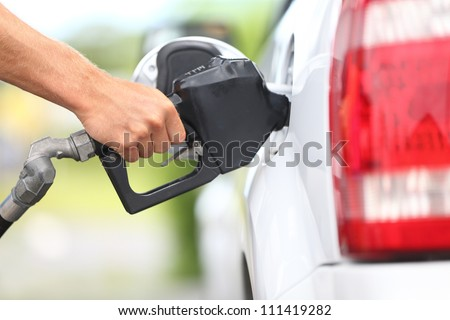 Pumping gas at gas pump. Closeup of man pumping gasoline fuel in car at gas station. - stock photo