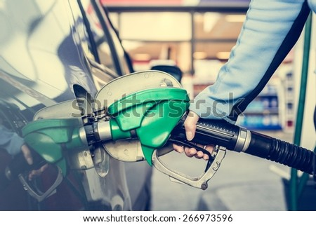 Pumping gas at gas station. Close up of a hand holding fuel nozzle. - stock photo