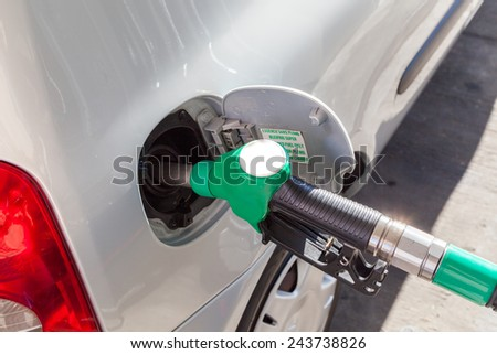 pumping gasoline fuel in car at gas station - enhanced colors - stock photo