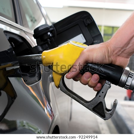 pumping gasoline on a black car in station - stock photo