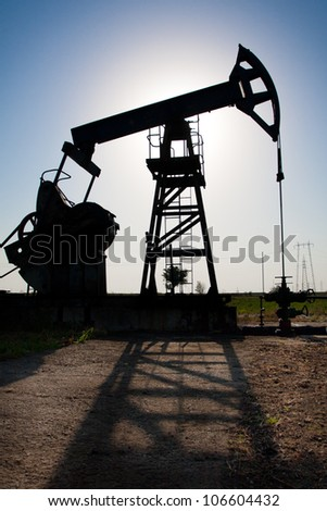 Pumpjack in the sunset - stock photo
