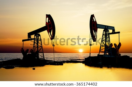 Pumpjack on the beach at sunset. - stock photo
