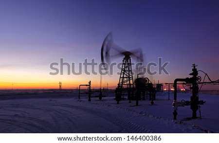 Pumpjack on the sunset sky background. Long exposure. Panorama. - stock photo