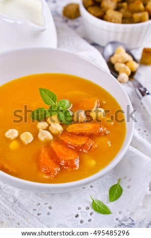 Pumpkin and carrot soup with chickpeas on a light background. Selective focus.