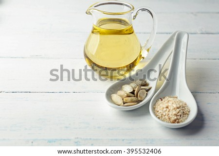 Pumpkin and sesame seeds with oil on wooden table - stock photo