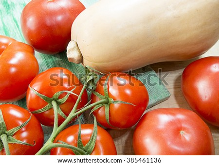 Pumpkin and tomatoes on a wooden table - stock photo