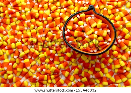 Pumpkin bowl filled with candy corn candies - stock photo