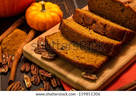 Pumpkin bread loaf sitting on wooden cutting board with pecan nuts and cinnamon spices - stock photo