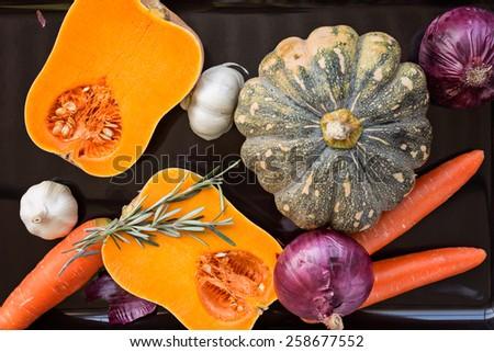 Pumpkin, carrot, onion, garlic and rosemary on black tray ready to roast - stock photo