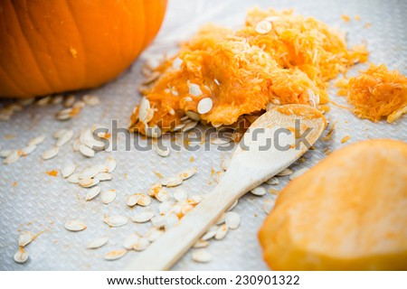 Pumpkin Carving - This is a shot of a pumpkin carving scene with all the seeds laying out on the table. - stock photo