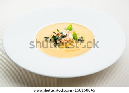 Pumpkin crab soup on a white bowl - stock photo