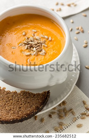 pumpkin creme soup with sunflower seeds and bread. Vertical image - stock photo