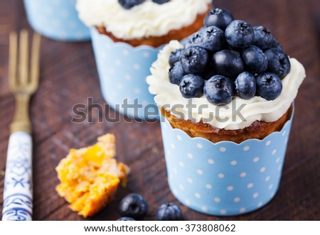 Pumpkin cupcakes decorated with cream cheese frosting and fresh blueberries on a wooden background - stock photo