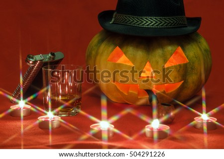 Pumpkin for Halloween with glowing eyes, smoking pipe and glass of whiskey by candlelight