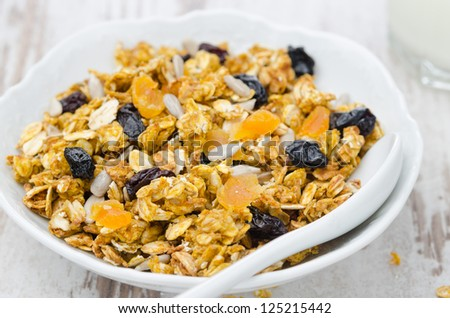 pumpkin granola with dried fruit and seeds in a white bowl closeup - stock photo