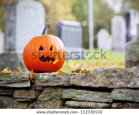 Pumpkin in graveyard with autumn leaves - stock photo