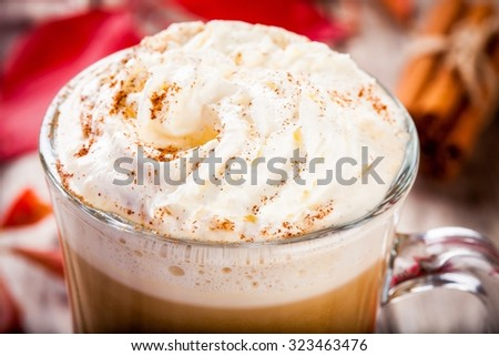 pumpkin latte with whipped cream in a glass jar closeup on a rustic background