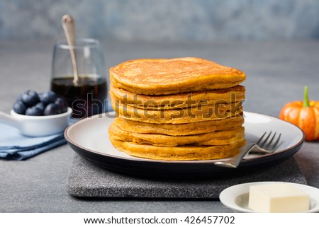 Pumpkin pancakes with maple syrup and blueberries on a plate. Grey stone background Copy space  - stock photo