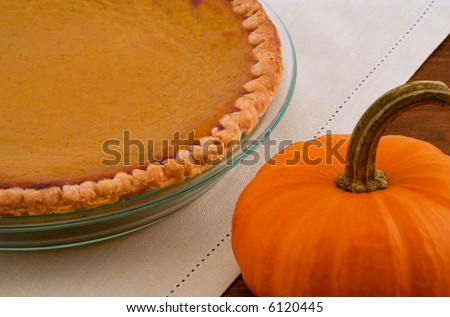 Pumpkin Pie and Pumpkin on Wood Table - stock photo